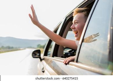 happy muslim boy waving outside car window