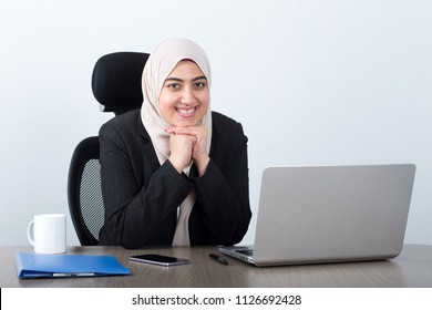 Happy Muslim business woman at work, isolated on a grey background.