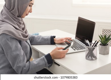 Happy muslim businesswoman in hijab at office workplace. Smiling Arabic woman working on laptop and messaging on smartphone, copy space