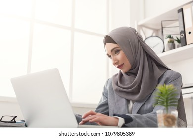 Happy muslim businesswoman in hijab at office workplace. Smiling Arabic woman working on laptop on startup project, copy space