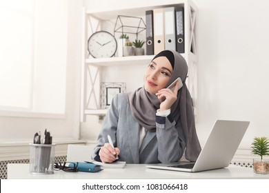 Happy muslim businesswoman in hijab at office workplace. Smiling Arabic woman talking on smartphone, making notes and working on laptop, copy space