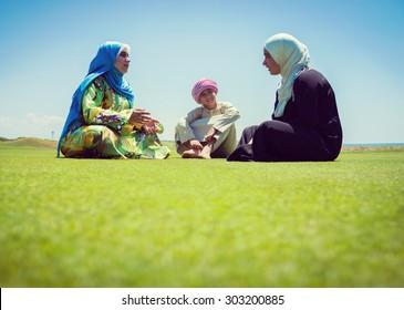 Happy Muslim family on green meadow