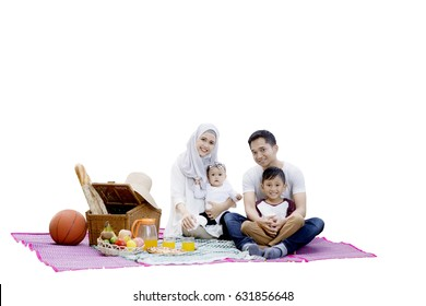 Happy muslim family picnicking together while sitting on mat with picnic basket and foods, isolated on white background