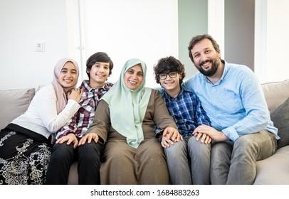 Happy Muslim family portrait on sofa