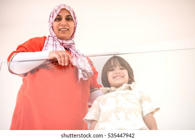 Happy Muslim Middle Eastern mother with son at new modern home family at new modern home
