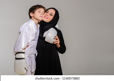 Happy Muslim mom with little son in kimono hugging after competition.