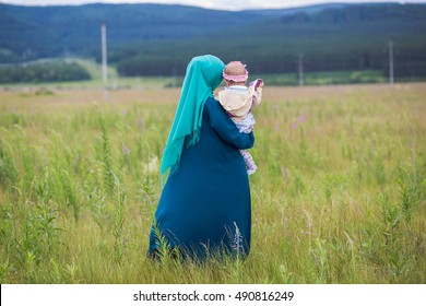 Happy Muslim woman with a baby.