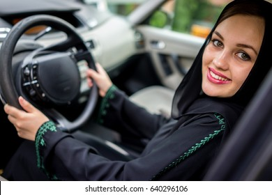 happy muslim woman driving car