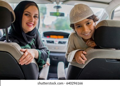 happy muslim woman and her son driving in a car