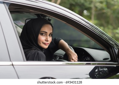 Happy muslim woman inside her new car.