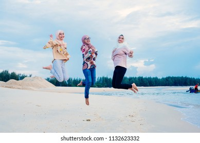 Happy Muslim women jumping near the beach
