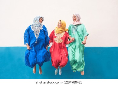 Happy muslim women jumping together outdoor - Arabian teen girls having fun in the city - concept of people,costume, culure and religion