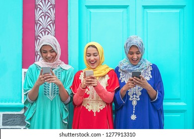 Happy muslim women using their mobile smart phones in the college - Arabian young people watching on cellphone and laughing together outdoor - Millennials, generation z and technology concept