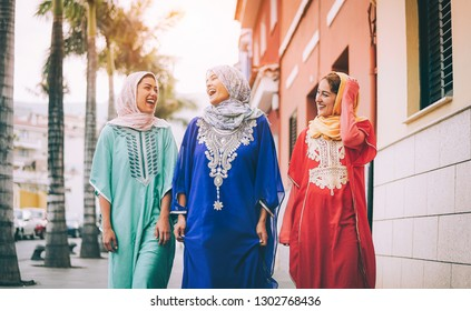 Happy Muslim women walking in the city center - Arabian young girls having fun spending time and laughing together outdoor - concept of people, culture and religion