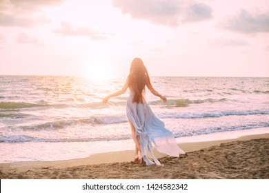 happy mysterious woman silhouette mermaid long black hair walks beach blue water of ocean, sea nymph  wind listening wave. long blue dress flying train, look divine sunset. Art photo from back no face