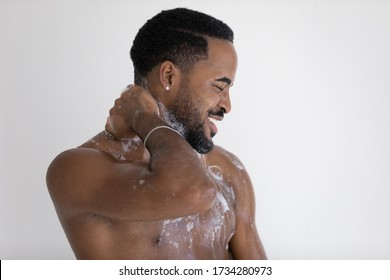 Happy naked african American man stand under water flow wash with foamy gel in home bathroom, smiling handsome young biracial male take morning daily shower in bath, body hygiene concept