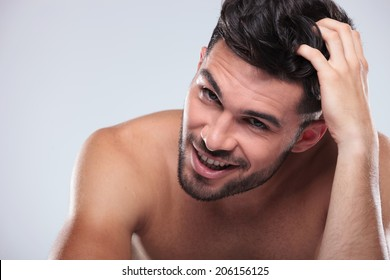 happy naked man scratching his head and smiles to the camera
