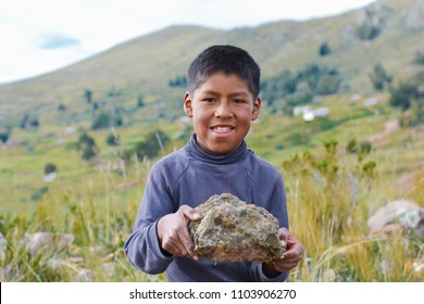 Happy native american boy holding big rock in the countryside.