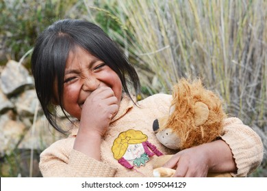 Happy native american girl of 7 years laughing, holding her lion toy and some bread.