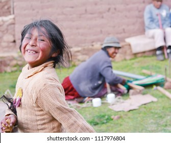 Happy native american girl holds pancake. Old age woman weaving traditional clothing in the background.