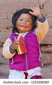 Happy native american little girl eating watermelon outside.