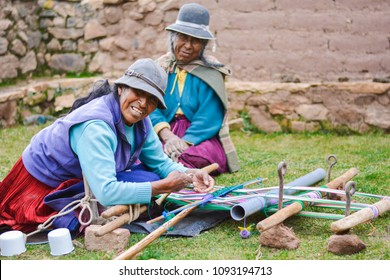 Happy native american mother and daughter weaving authentic aymara cloth.