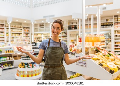 Happy natural young saleswoman in supermarket. Front of display of fruits. Open arms