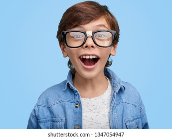 Happy nerdy boy in eyeglasses and denim jacket looking excitedly at camera on blue background . Closeup portrait of Excited school kid in broken glasses