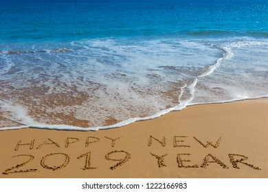 HAPPY NEW 2019 YEAR inscription written in the wet yellow beach sand. Concept of celebrating the New Year.