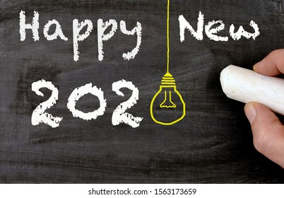 Happy new 2020 chalkboard, lightbulb and a hand
