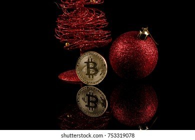 Happy New Bitcoin year! Two Virtual Coins Bitcoins and red Christmas ball / bauble on dark black background.  Isolated