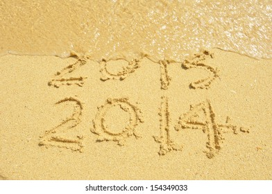 Happy New Year 2014 replace 2013 concept on the sea beach
