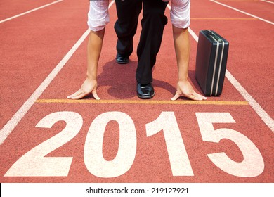 happy new year 2015. businessman preparing for running with briefcase