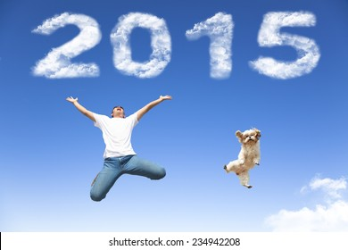 happy new year 2015.young man and dog  jumping together with blue sky background