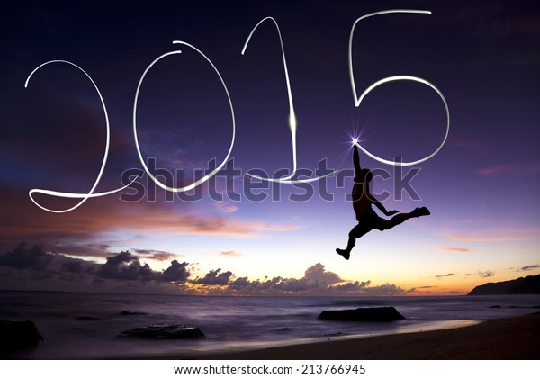 happy new year 2015.young man jumping and drawing 2015 by flashlight