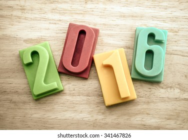 Happy new year 2016, bar of chocolate number on wooden background, Vintage color effect