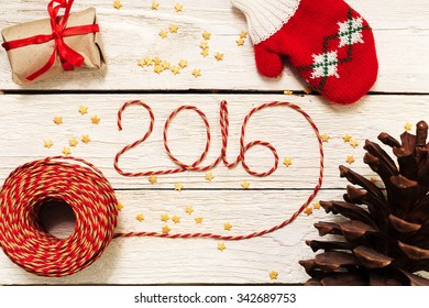 Happy New year 2016, numbers maden by wrapping thread of yarn on wooden background with Christmas decorations
