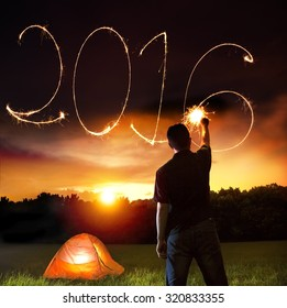happy new year 2016.young man drawing by sparkler