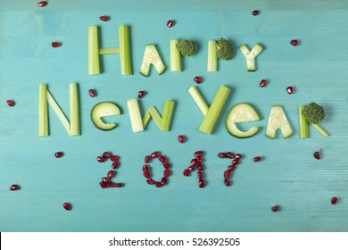 Happy New Year 2017, food lettering, vegetable word on blue wooden background with berries