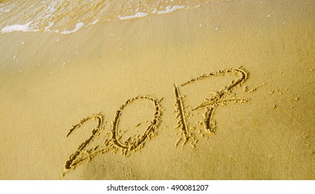 happy new year. 2017 inscription written on sandy beach with wave approaching.