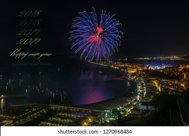 Happy new year & 2018 to 2019 progression in golden letters combined to a night scene of a enlightened town & impressive blue & red fireworks reflecting to the sea