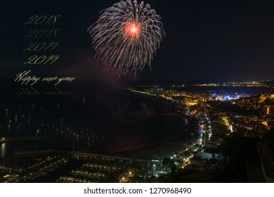 Happy new year & 2018 to 2019 progression in golden letters combined to a night scene of a enlightened town & eye shape-like fireworks