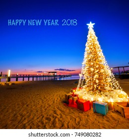 HAPPY NEW YEAR,  2018, Christmas tree with lighting on the beach.