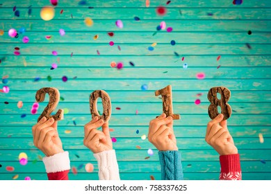 Happy New Year 2018! Confetti falling against wooden background