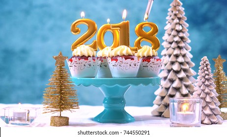 Happy New Year 2018 cupcakes on a modern stylish, festive, blue gold and white Winter theme table setting, close up with copy space lighting candles.