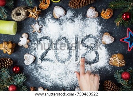 Happy New Year 2018 written on flour and Christmas Decorations Gingerbread cookies on dark stone background. Christmas card, New Year greeting card