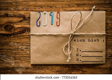 Happy new year 2019 - clips on paper envelope with rope lie on wooden table. Christmas background. holiday background. envelope wishes for Santa Clause. wish list for Santa Claus inside