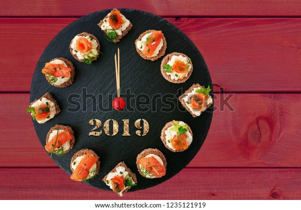 Happy New Year 2019! Clock showing  12 o'clock, creative food idea with smoked salmon canapes on black slate platter as clock face over dark red wooden background.