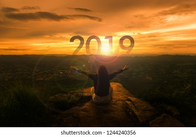 Happy New year 2019 concept : Yong sitting over the cliff and raise the hand up on sunset time