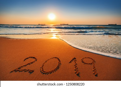 Happy New Year 2019 concept, lettering on the beach. Sea sunrise.